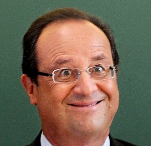 French President Francois Hollande smiles as he chairs a round table discussion on the changes in the school timetable set out by the government during a visit to the primary school Michelet on the first day of the new school year in Denain
