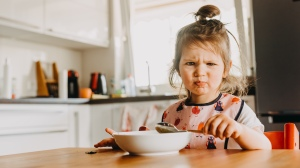 adorable funny toddler girl looks unhappy with her meal